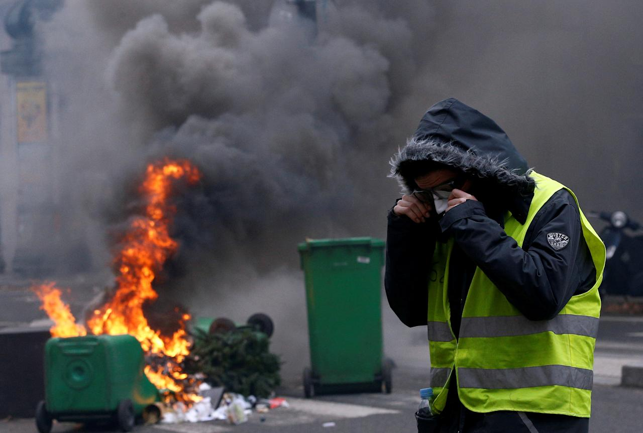 "A protester wearing a yellow vest stands next to burning trash bins in a street during clashes with police at a national day of protest by the ""yellow vests"" movement in Paris, France, December 8, 2018. REUTERS/Stephane Mahe     TPX IMAGES OF THE DAY"
