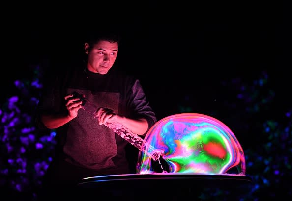 Bubble artist Deni Yang performs his act during his Mega Bubblefest Laser Show at the Discovery Cube Science Center in Santa Ana, California, on April 4, 2018. Deni is the son of famed bubble master Fan Yang. His family holds the world record for largest soap bubble measuring 167-foot-long that was created in Beijing, China in 2009. / AFP PHOTO / Mark Ralston (Photo credit should read MARK RALSTON/AFP/Getty Images)