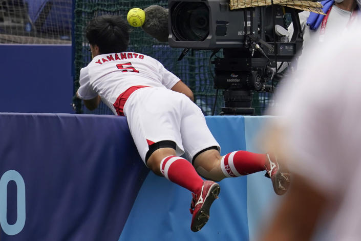 Japan's Yu Yamamoto (5) reaches over a wall for a foul ball hit by United States' Amanda Chidester in the sixth inning of a softball game at the 2020 Summer Olympics, Monday, July 26, 2021, in Yokohama, Japan. (AP Photo/Sue Ogrocki)
