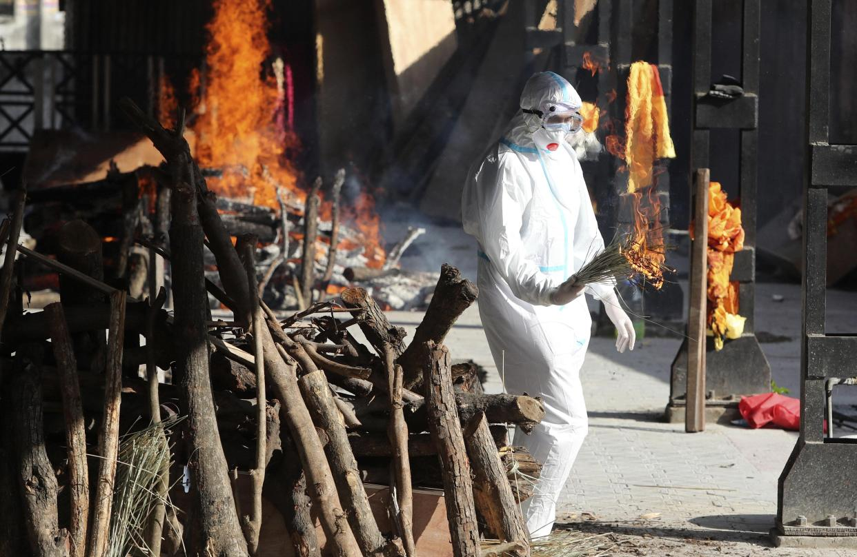 A family member performs the last rites for a COVID-19 victim at a crematorium in Jammu, India, Friday, April 23, 2021. India's underfunded health system is tattering as the world's worst coronavirus surge wears out the nation, which set another global record in daily infections for a second straight day with 332,730. India has confirmed 16 million cases so far, second only to the United States in a country of nearly 1.4 billion people. (AP Photo/Channi Anand)