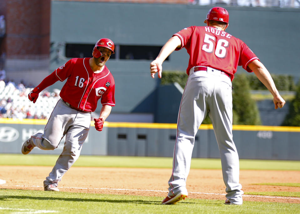 Cincinnati Reds Tucker Barnhart (16) rounds third and reacts with third base/catching coach J.R. House (56) after hitting a three-run home run in the tenth inning of a baseball game against the Atlanta Braves, Sunday, Aug.4, 2019, in Atlanta. (AP Photo/Todd Kirkland)