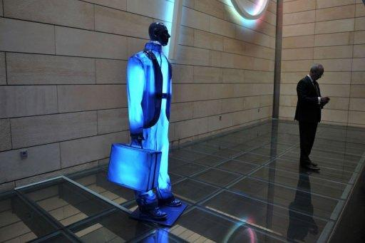 A man looks at his mobile phone by a sculpture of a banker at the National Bank of Greece premises on November 14