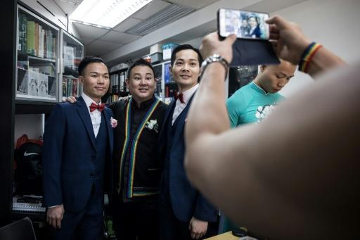 Apprehensive about holding a wedding ceremony in the socially conservative city a year after they signed marriage papers in Britain, Chan (L) and So (centre R) were finally convinced by their pastor to hold a small-scale celebration