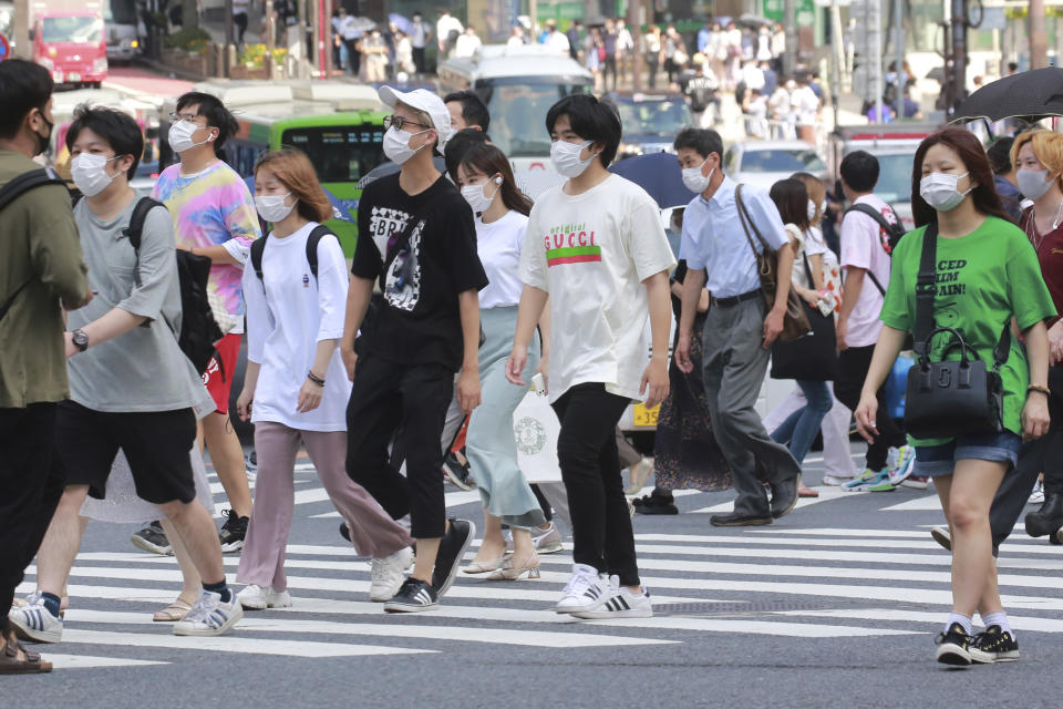 People wearing face masks to help protect against the spread of the coronavirus walk across an intersection in Tokyo Monday, Aug. 30, 2021. (AP Photo/Koji Sasahara)
