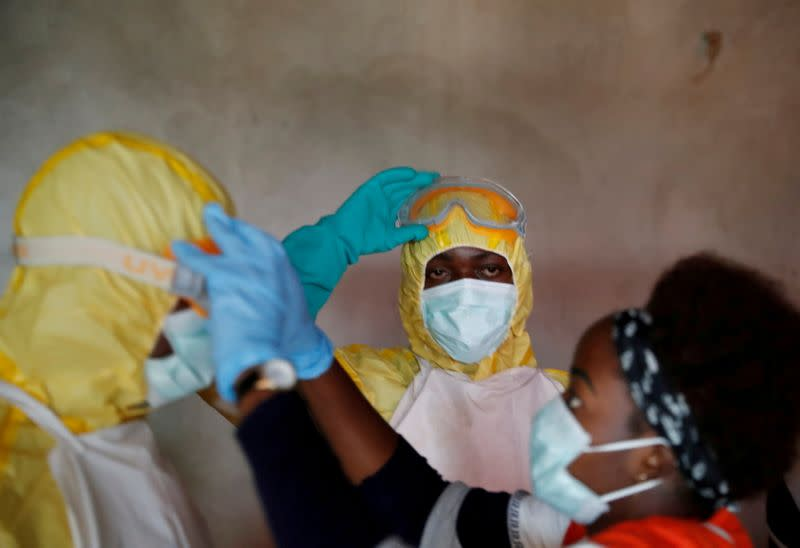 FILE PHOTO: Healthcare workers adjust gear during a funeral of a person who is suspected of dying of Ebola in Beni,