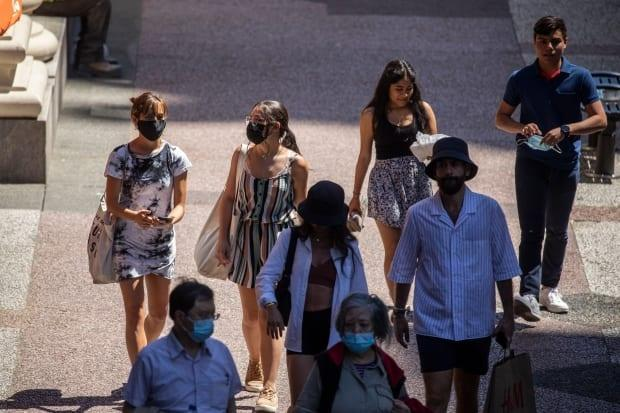 People are seen walking down a sidewalk in downtown Vancouver on Tuesday, June 22, 2021.  (Ben Nelms/CBC - image credit)