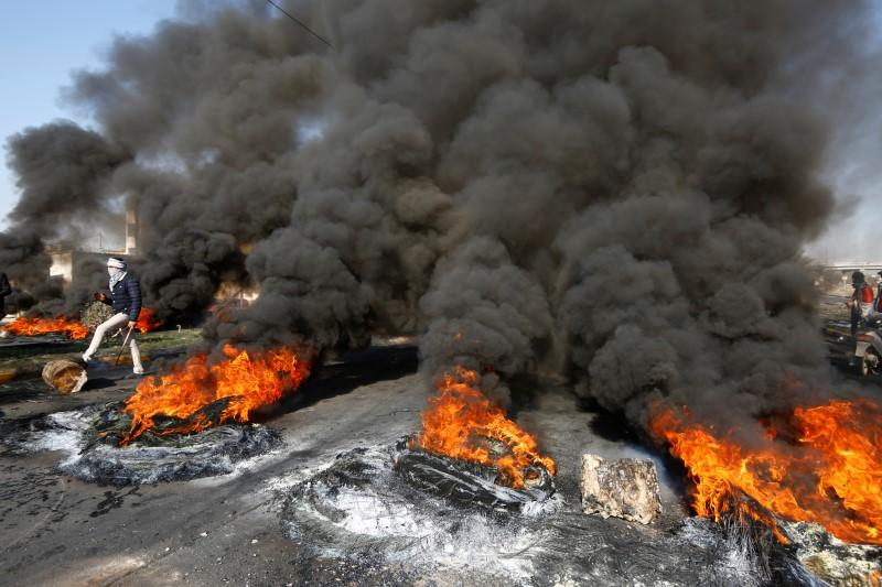 Smoke rises from burning tires ignited by Iraqi demonstrators to block a road during ongoing anti-government protests in Najaf