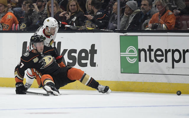 Chicago Blackhawks left wing Alex DeBrincat, top, and Anaheim Ducks left wing Nick Ritchie watch the puck during the third period of an NHL hockey game Wednesday, Feb. 27, 2019, in Anaheim, Calif. The Blackhawks won 4-3. (AP Photo/Mark J. Terrill)