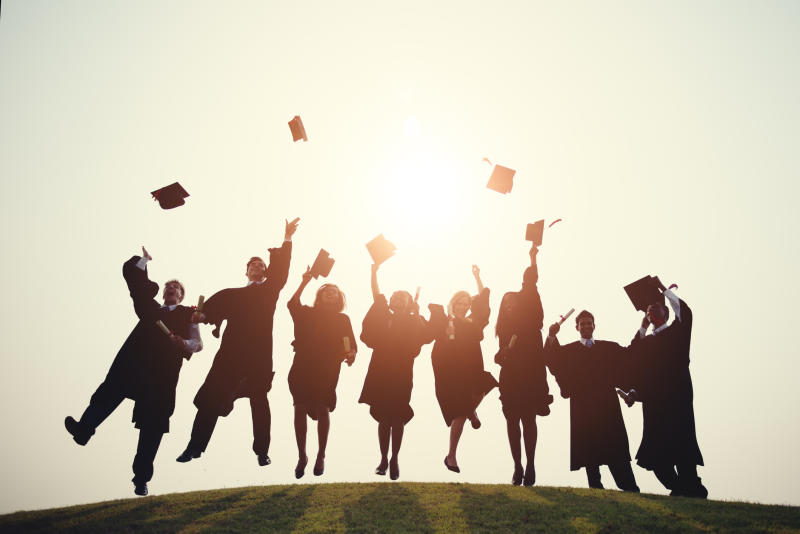 Graduates in robes throw their hats in the air.