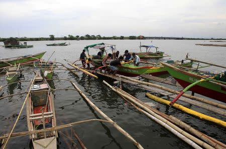 Residents secures small boat in safer area in preparations for strong winds brought by Typhoon Rammasun, locally name Glenda, in coastal area of Cavite city, south of Manila