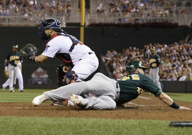 Oakland Athletics' Josh Donaldson, right, scores on a single by Yoenis Cespedes as Minnesota Twins catcher Josmil Pinto waits for the throw in the sixth inning of a baseball game, Tuesday, Sept. 10, 2013, in Minneapolis. The Twins won 4-3. (AP Photo/Jim Mone)