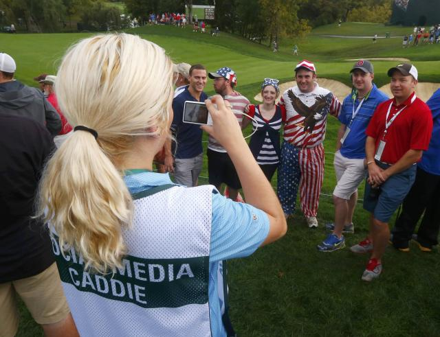 A Social Media Caddie takes a picture of golf fans with a phone during the continuation of the rain delayed Foursome matches for the 2013 Presidents Cup golf tournament at Muirfield Village Golf Club in Dublin, Ohio October 6, 2013. REUTERS/Jeff Haynes (UNITED STATES - Tags: SPORT GOLF)