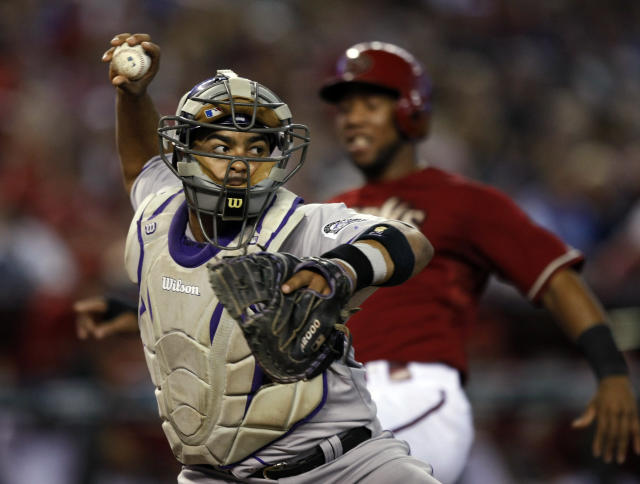 Colorado Rockies catcher Wilin Rosario (20) gets the force out and then commits an throwing error in the fourth inning during a baseball game against the Arizona Diamondbacks Sunday, Aug. 10, 2014, in Phoenix. (AP Photo/Rick Scuteri)