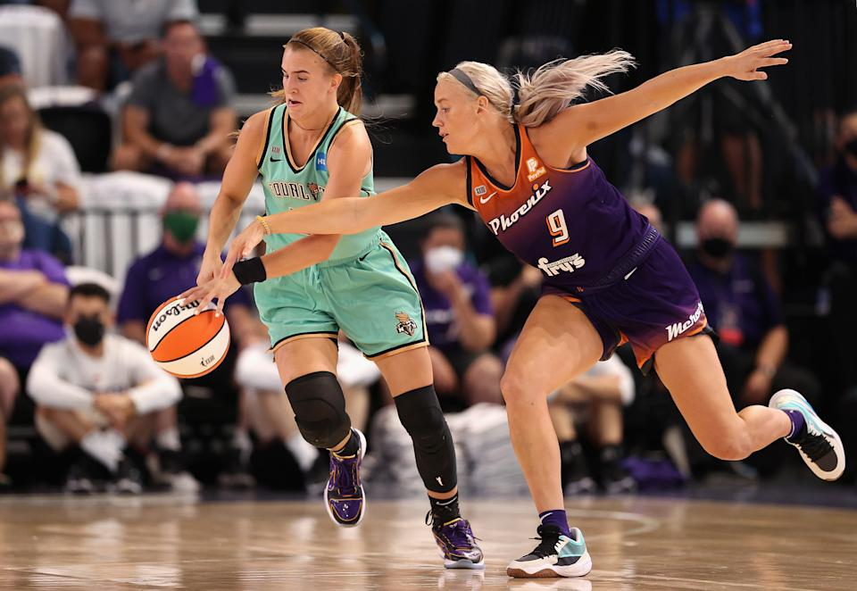 New York's Sabrina Ionescu controls the ball under pressure from Phoenix's Sophie Cunningham during the first half of their first-round WNBA playoff game at Grand Canyon University Arena in Phoenix on Sept. 23, 2021. (Christian Petersen/Getty Images)