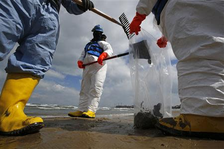 Oil spill response contractors clean up crude oil on a beach after a BP oil spill on Lake Michigan in Whiting, Indiana March 25, 2014. REUTERS/Jim Young