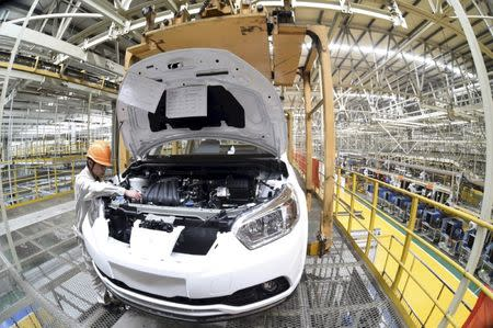 File picture of an employee working along a production line at a factory of Dongfeng Nissan Passenger Vehicle Co. in Zhengzhou