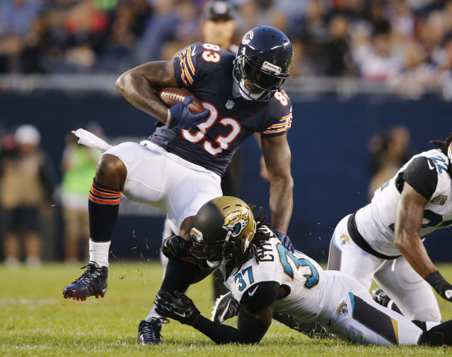 Chicago Bears tight end Martellus Bennett (83) is tackled by Jacksonville Jaguars safety Johnathan Cyprien (37) during the first half of an NFL preseason football game in Chicago, Thursday, Aug. 14, 2014. (AP Photo/Stacy Thacker)