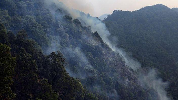 Smoke billows from forest fires after helicopters dump water on them