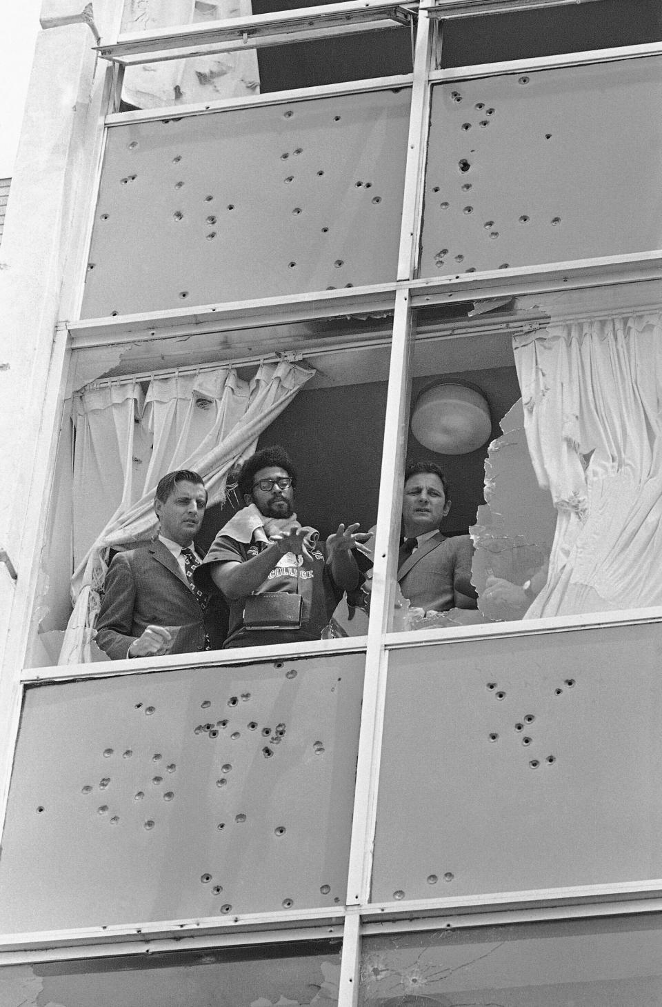 FILE - In this May 20, 1970, file photo, U.S. Sens. Walter Mondale, D-Minn., left, and Birch Bayh, D-Ind., right, look from the shattered windows of Alexander Hall, a women's dormitory, during a visit to Jackson State College, in Jackson, Miss., days after an assault by local white police and members of the Mississippi Highway Patrol, who claimed they had seen a sniper. Pointing out the view is student Carl Griffin. The historically Black school canceled its 1970 commencement after the violent incident. Fifty-one years later, the school now called Jackson State University is honoring its Class of 1970, as members are being invited back to salute their academic achievements with a graduation ceremony on Saturday, May 15, 2021. (AP Photo, File)