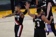 Portland Trail Blazers guard Damian Lillard (0) and guard CJ McCollum (3) celebrate after a score during the fourth quarter of the team's NBA basketball game against the Los Angeles Lakers on Monday, Dec. 28, 2020, in Los Angeles. (AP Photo/Ashley Landis)