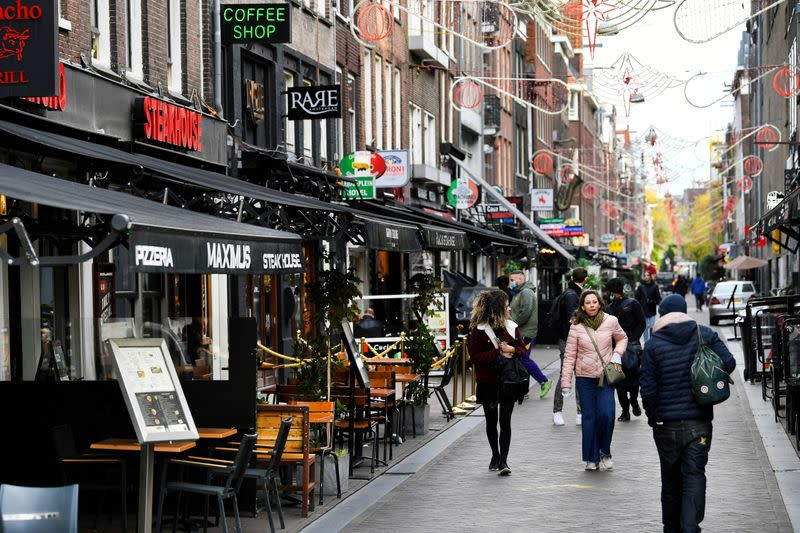 FILE PHOTO: People walk past restaurants and bars following the new social restrictions announced by the Dutch government, as the Netherlands battle to control the spread of the coronavirus disease (COVID-19), in Amsterdam,