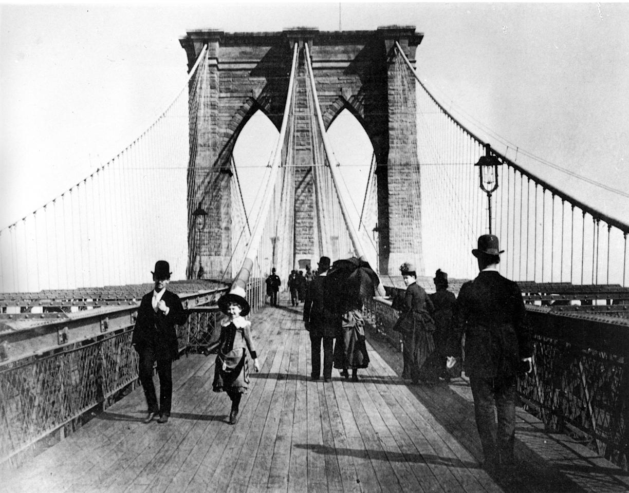 Pedestrians stroll along the promenade of the Brooklyn Bridge, connecting Manhattan and Brooklyn, New York City, 1891.  The suspension bridge was opened to traffic on May 24, 1883.  When bridge designer John A. Roebling incorporated the promenade into the design of the bridge, he said it was important that the people take part in the leisures afforded by the bridge.  (AP Photo)