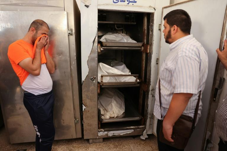 The distraught brother of Eyad Saleha, a 33-year-old disabled Palestinian who was killed along with his pregnant wife and three-year-old daughter, weeps in front of the corpses at the morgue