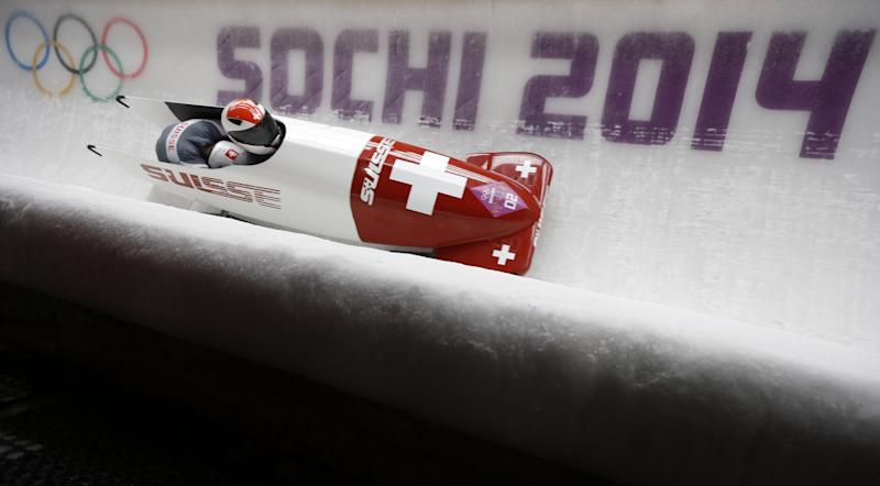 The team from Switzerland SUI-1, piloted by Beat Hefti and brakeman Alex Baumann, take a curve during the men's two-man bobsled competition at the 2014 Winter Olympics, Sunday, Feb. 16, 2014, in Krasnaya Polyana, Russia. (AP Photo/Natacha Pisarenko)