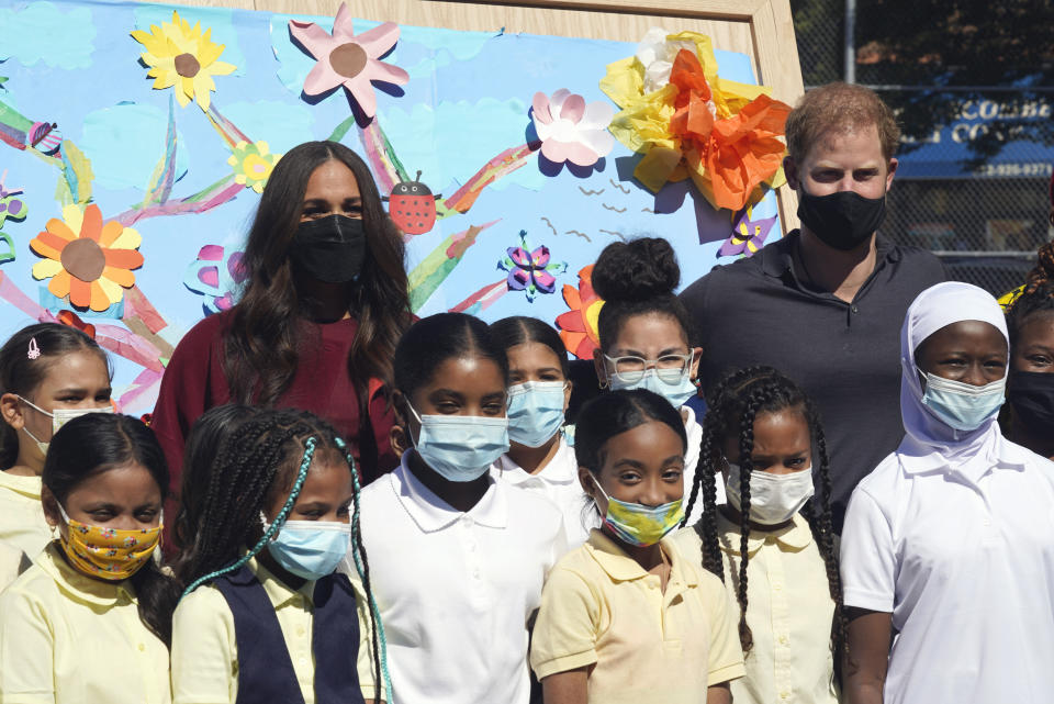 Prince Harry and Meghan, the Duke and Duchess of Sussex, pose for photos with a group of third grade students during their visit to P.S. 123, the Mahalia Jackson School, in New York's Harlem neighborhood, Friday, Sept. 24, 2021. (AP Photo/Richard Drew)