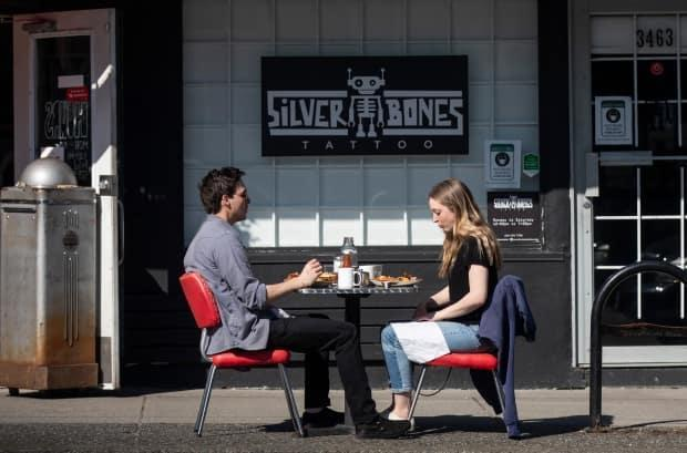 Two people eat at a table on a sidewalk outside a restaurant in Vancouver on April 15.  (Ben Nelms/CBC - image credit)