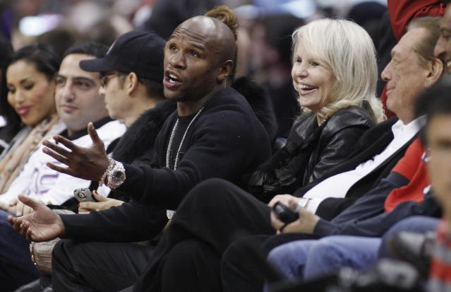 U.S. boxer Floyd Mayweather Jr.,sits courtside with Los Angeles Clippers owner Donald Sterling (R) and Sterling's wife Shelly (2nd R) at the NBA basketball game between the Chicago Bulls and Los Angeles Clippers in Los Angeles in this December 30, 2011 file photo. Mayweather Jr., one of boxing's biggest names, expressed interests in the team in comments to reporters in Las Vegas ahead of a May 3 bout after the NBA announced a lifetime ban of owner Sterling from pro basketball over racist comments the league said he acknowledged making. REUTERS/Danny Moloshok/Files (UNITED STATES - Tags: SPORT BASKETBALL BOXING ENTERTAINMENT BUSINESS)