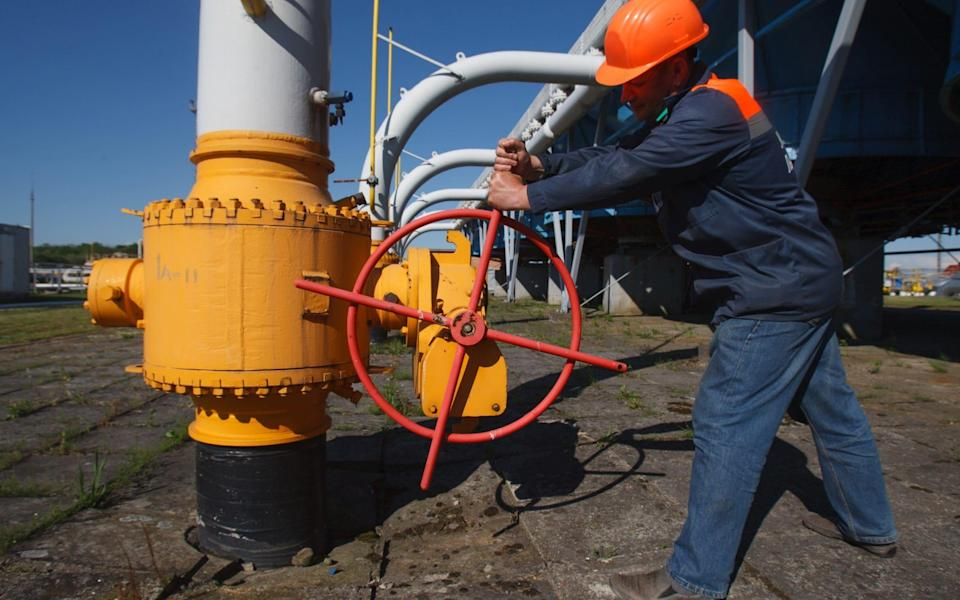 A worker tightens the valve on a pipeline at an underground gas storage facility in Ukraine - AFP