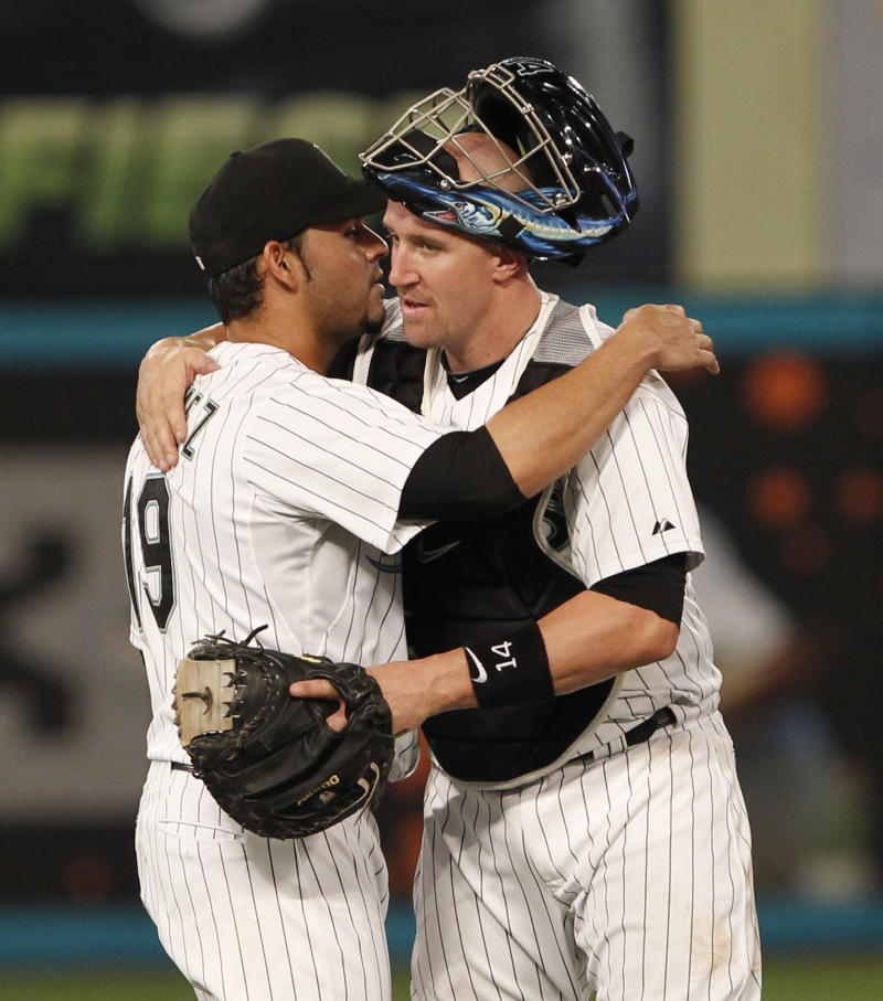 ** CORRECTS TO ROCKIES' DEXTER FOWLER NOT OMAR INFANTE ** Florida Marlins starting pitcher Anibal Sanchez, left, is hugged by catcher John Buck after the Marlins defeated the Colorado Rockies 4-1 in a baseball game on Friday, April 22, 2011, in Miami. Rockies' Dexter Fowler singled to lead off the ninth inning for the only hit against Sanchez in the game. (AP Photo/Wilfredo Lee)