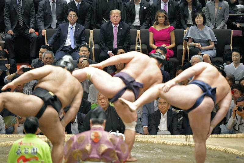 FILE - In this May 26, 2019, file photo, U.S. President Donald Trump, center back, and first lady Melania Trump, second right back, accompanied by Japanese Prime Minister Shinzo Abe, left, and his wife Akie Abe watch the ring-entering ceremony of sumo wrestlers during an annual summer sumo wrestling championship at the Ryogoku Kokugikan sumo arena in Tokyo. Sumo wrestling is going to get some extra attention because of the Tokyo Olympics. The Japan Sumo Association and local Olympic organizers are planning a sumo tournament on Aug. 12-13, just days after the Olympics end. (Kyodo News via AP)