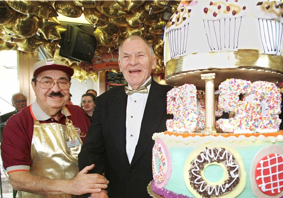 Dunkin' Donuts founder Bill Rosenberg, right, poses with Dunkin' Donuts pitchman Michael Vale, left, Wednesday, March 1, 2000, in Boston, during a 50th anniversary celebration for Dunkin' Donuts.  (AP Photo/Angela Rowlings)