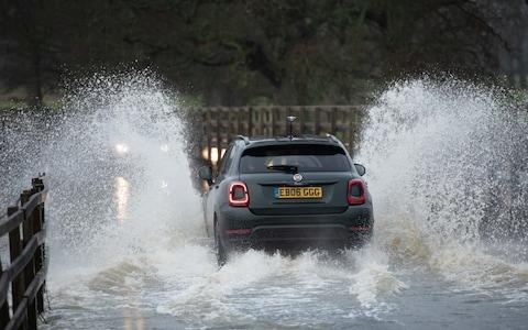 A car drives over a flooded bridge in Wiltshire - Credit: Lee Thomas