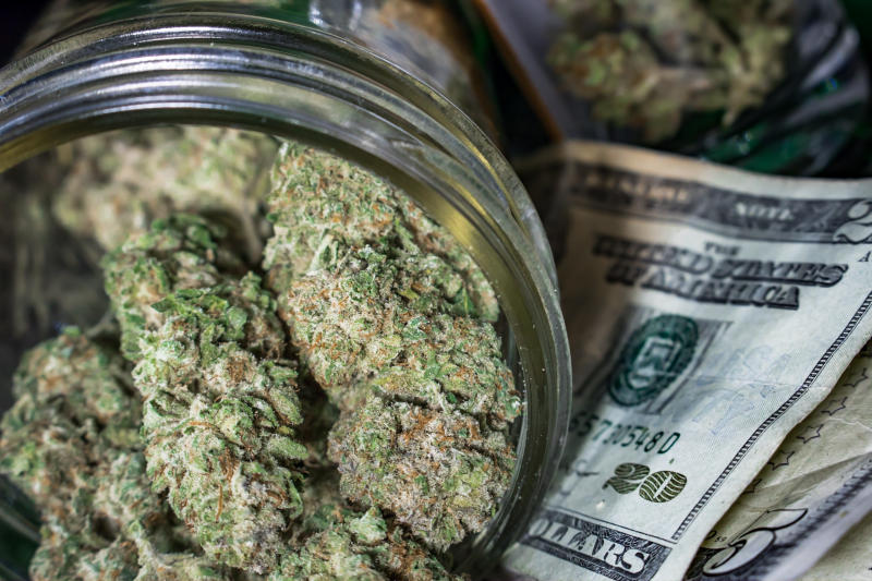 A tipped over clear jar packed with cannabis buds that's lying atop a small pile of cash bills.