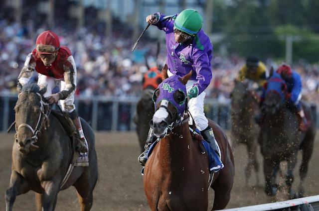 Jockey Victor Espinoza, center, aboard California Chrome, celebrates after winning the 139th Preakness Stakes horse race at Pimlico Race Course, Saturday, May 17, 2014, in Baltimore. Ride On Curlin, left, ridden by Joel Rosario, finished second. (AP Photo/Matt Slocum)