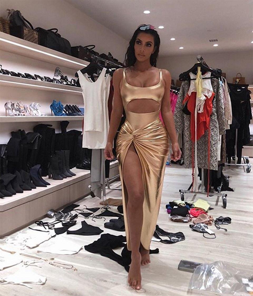 Kim's closet is possibly the most well-known area in their home, as she often posts pictures of her fittings that happen there. In one, in which she sports a gold cutout dress, racks of clothes and streamlined shelves of shoes and purses are visible behind her.