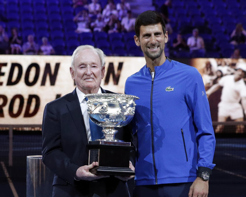 FILE - In this Jan. 14, 2019, file photo, Serbia's Novak Djokovic, right, presents a trophy to Rod Laver during the 50th anniversary celebration for the Australian Open and Laver's second Grand Slam at the Australian Open tennis championships in Melbourne, Australia. If Djokovic wins the U.S. Open to complete the first calendar-year Grand Slam in men's tennis in 52 years, Laver will be there to welcome him into a remarkably exclusive club. (AP Photo/Aaron Favila, File)