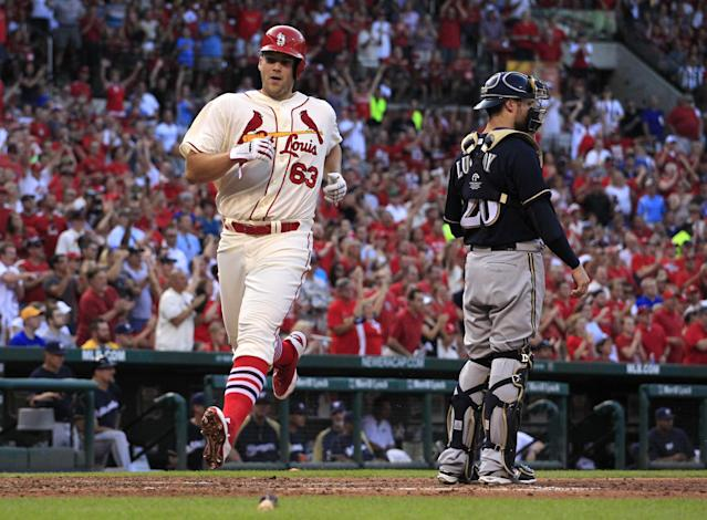 St. Louis Cardinals' Justin Masterson, left, scores past Milwaukee Brewers catcher Jonathan Lucroy on a two-run single by Kolten Wong during the second inning of a baseball game Saturday, Aug. 2, 2014, in St. Louis. (AP Photo/Jeff Roberson)