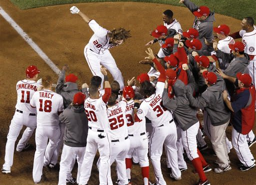 Jayson Werth leaps onto home plate after hitting a walk-off home run to force a Game 5. (AP)