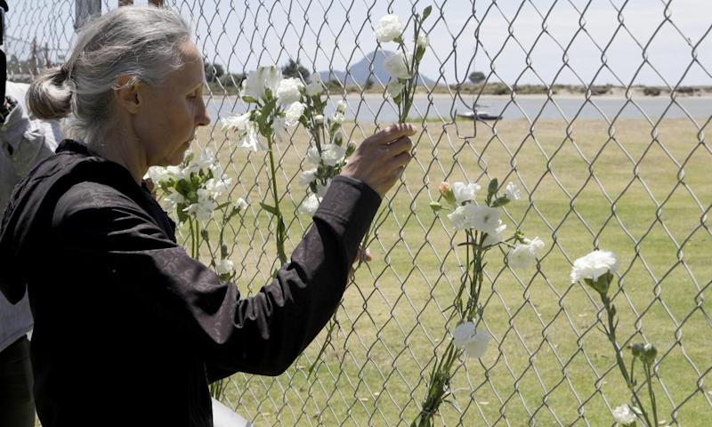 A woman places flowers at a fence on the waterfront in Whakatāne.