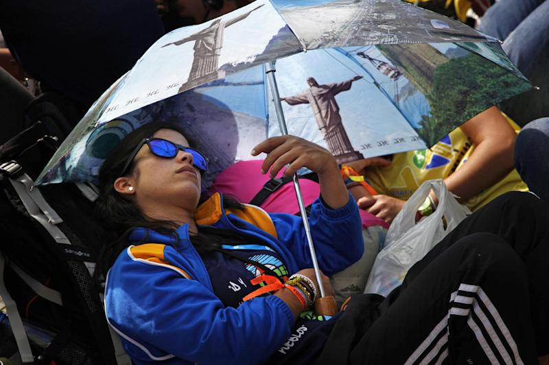 A pilgrim rests under an umbrella decorated with images of the Christ the Redeemer statue as she waits on Copacabana beach for an evening vigil with Pope Francis during World Youth Day events in Rio de Janeiro, Brazil, Saturday, July 27, 2013. Francis will preside over an evening vigil service on Copacabana beach that is expected to draw more than 1 million young people. (AP Photo/Jorge Saenz)