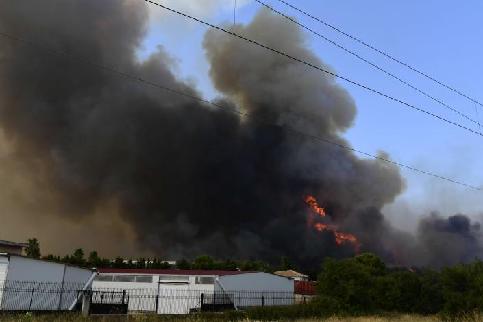 Flames burn near buildings outside an Air Base in Tatoi area, northern Athens, Greece, Tuesday, Aug. 3, 2021. Hundreds of residents living near a forest area north of Athens fled their homes Tuesday as a wildfire reached residential areas as Greece grappled with its worst heatwave in decades. (AP Photo/Michael Varaklas)