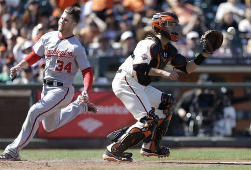 Washington Nationals' Bryce Harper, left, scores behind San Francisco Giants catcher Buster Posey in the 10th inning of a baseball game Wednesday, May 22, 2013, in San Francisco. Harper scored on a hit by Nationals' Ian Desmond. (AP Photo/Ben Margot)