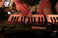 Musician Francesco Perini, sanitizes his keyboards prior to his live socially distanced performance at the Moth Club in Hackney, in London, Sunday, May 30, 2021. The return of live music in the city that produced bands from the Rolling Stones to the Spice Girls has reignited the creativity of some of London's many working artists after 14 months of silence. (AP Photo/Alberto Pezzali)