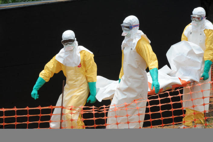 """Staff of the """"Doctors without Borders"""" medical aid organisation carry the body of a person killed by viral haemorrhagic fever, at a center for victims of the Ebola virus in Guekedou, Guinea on April 1, 2014 (AFP Photo/Seyllou)"""