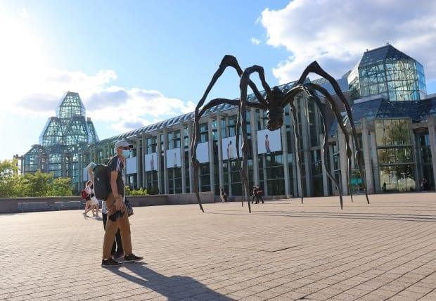 A photographer wearing a mask stands near the statue of Maman outside the National Gallery of Canada in Ottawa on Thursday. On Saturday, health officials in the nation's capital reported 65 new cases of COVID-19.  (Trevor Pritchard/CBC - image credit)