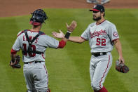 Washington Nationals relief pitcher Brad Hand (52) and catcher Yan Gomes (10) celebrate following a baseball game against the St. Louis Cardinals Monday, April 12, 2021, in St. Louis. (AP Photo/Jeff Roberson)